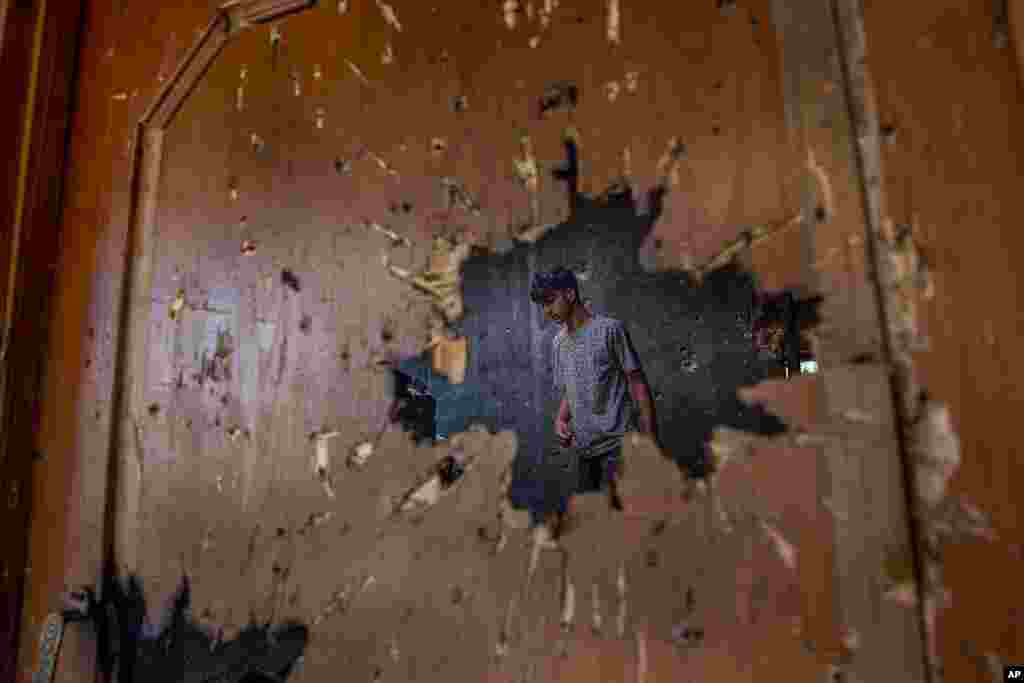 A Kashmiri, inspecting a house where suspected rebels had taken refuge, is seen through a hole created by a mortar shell fired by government forces during a gunfight, in Srinagar, Indian controlled Kashmir.