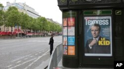 A police officer stands guard next to a newsstand displaying the cover of a news magazine depicting French president-elect Emmanuel Macron on the Champs Elyses avenue in Paris, France, May 8, 2017.