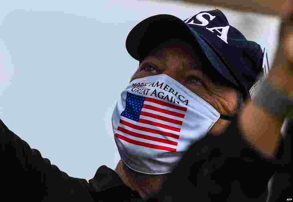 """Поддржувач на Доналд Трамп носи маска со слоганот """"Да ја направиме Америка повторно голема"""" на протест на кој се бара отворање на Флорида во Мајами. (CHANDAN KHANNA / AFP)"""