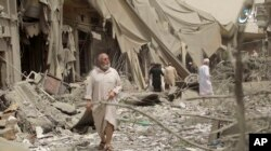 Arhiva - Kadar video snimka koji je objavila Amaq novinska agencija, medijski servis Islamske države, na kome se vide ljudi kako pregledaju ruševine nastale vazdušnim udarima i granatiranjem u serernosirijskom gradu Raki