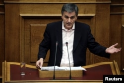 Greek Finance Minister Euclid Tsakalotos delivers a speech during a parliamentary session before a budget vote in Athens, Greece, Dec. 10, 2016.