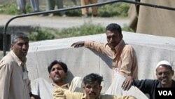 Warga Abbottabad, Pakistan, duduk-duduk di atas reruntuhan yang ditutup terpal, Senin (2/5). Reruntuhan tersebut berasal dari lokasi kompleks tempat persembunyian bin Laden.