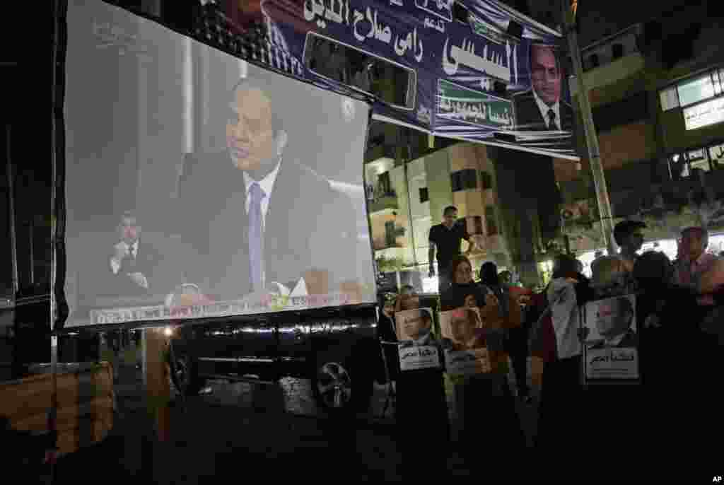 Supporters of former army chief Abdel-Fattah el-Sissi watch his first televised interview on a big screen, Cairo, May 5, 2014.