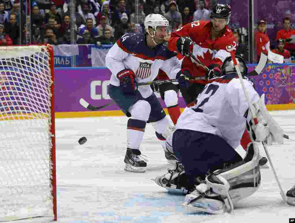 Canada forward Benn Jamie, right, shoots and scores against USA goaltender Jonathan Quick during the second period of a men's semifinal ice hockey game at the 2014 Winter Olympics, Feb. 21, 2014.