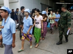 After a raid conducted by Thailand's Department of Special Investigation, soldiers and police escort Burmese workers from a shrimp shed in Samut Sakhon, Nov. 9, 2015.