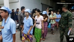FILE - After a raid conducted by Thailand's Department of Special Investigation, soldiers and police escort Burmese workers from a shrimp shed in Samut Sakhon, Nov. 9, 2015.