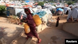 FILE - An internally displaced Somali girl carries a jerry-can of water as she walks through their makeshift shelters at Sayyidka camp in the Howlwadag district, south of Somalia's capital Mogadishu.