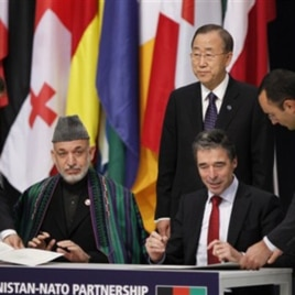Afghan President Hamid Karzai and NATO Secretary General Anders Fogh Rasmussen sign a declaration between NATO and the Afghan government on enduring partnership, as UN General Secretary Ban ki-Moon, centre, looks on at the NATO summit in Lisbon (file phot