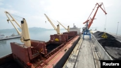 FILE - A cargo ship is loaded with coal during the opening ceremony of a new dock at the North Korean port of Rajin. The dock was jointly built with Russia after last year's completion of a railway link to North Korea.