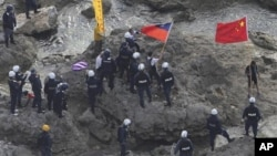 Chinese activists holding the flags of China and Taiwan are arrested by Japanese police officers on one of the disputed islands on August 15, 2012.