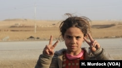 Initially told by IS militants that Shia-led forces would attack them in a fit of violence, local children flash victory signs at passing Hashd Shaabi vehicles, near Bashmana, Iraq, Dec. 16, 2016.