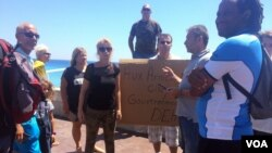 """A small far-right protest gathers near the memorial for the victims of the attack in Nice, France, calling on the government to """"arm the citizens"""" and sparking loud arguments, July 16, 2016. (H.Murdock/VOA)"""