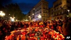 Un multitud de gente se reunió en torno a un memorial de flores, mensajes y velas por las víctimas del ataque en Barcelona, España.