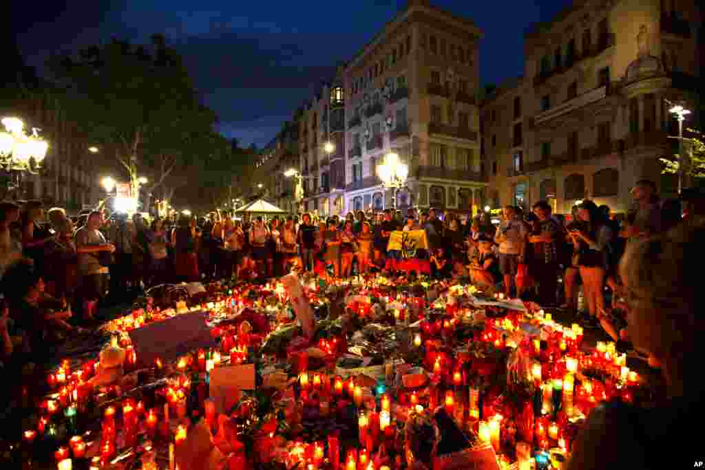 People gather at a memorial tribute of flowers, messages and candles to the victims on Barcelona's historic Las Ramblas promenade where the van stopped after killing at least 13 people in Barcelona , Spain.