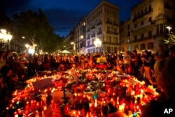 People gather at a memorial tribute of flowers, messages and candles to the victims on Barcelona's historic Las Ramblas promenade on the Joan Miro mosaic, embedded in the pavement where the van stopped after killing at least 13 people in Barcelona , Spain.