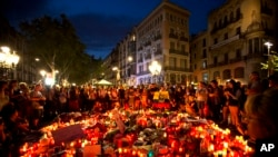 People gather at a memorial tribute of flowers, messages and candles to the victims on Barcelona's historic Las Ramblas promenade on the Joan Miro mosaic, embedded in the pavement where the van stopped after killing at least 13 people in Barcelona , Spain, Friday, Aug. 18, 2017. (AP Photo/Emilio Morenatti)