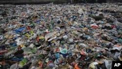 2018年6月4日,一名男子在印度孟買堆滿塑料和其它垃圾的阿拉伯海岸上行走。