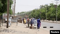 Quelques personnes marchent sur cette avenue après avoir fui une attaque de Boko Haram à Maiduguri dans l'Etat de Borno, Nigeria, 14 mai 2015.