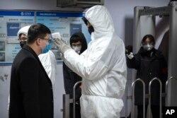 Seorang petugas medis mengenakan baju hazmat memeriksa suhu tubuh seorang penumpang di pintu masuk stasiun bawah tanah di Beijing, China, 26 Januari 2020.