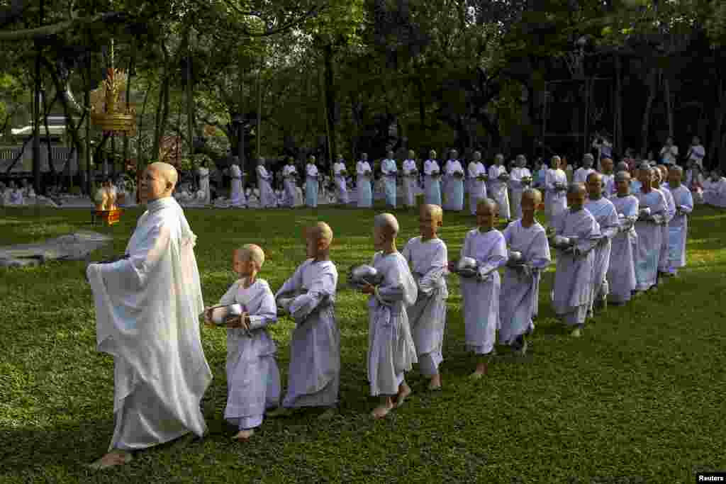 A Buddhist nun walks in line with novice nuns to receive food from people during the Songkran Festival at the Sathira-Dhammasathan Buddhist Meditation Center in Bangkok, Thailand.