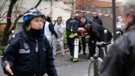 Nhân viên cứu hỏa đưa một nạn nhân ra khỏi hiện trường sau vụ nổ súng tại tòa soạn tuần báo Charlie Hebdo ở Paris, ngày 7/1/2015.