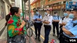 住在佐敦封鎖區內的尼泊爾籍居民Rai在社區封鎖前離家上班,她下班返家才知道當局已經實施封區禁足強制檢測,她向在場駐守的警員查詢如何返回封鎖區內。(美國之音 湯惠芸拍攝)