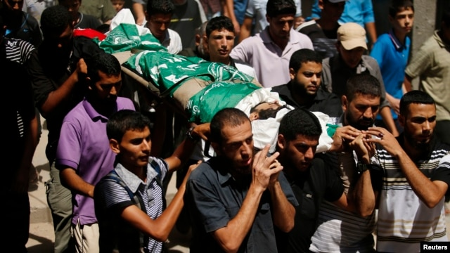 FILE - A new poll shows strong Palestinian support for Hamas' strategy of armed struggle against Israel. Palestinians carry the body of a Hamas militant killed in an Israeli airstrike in Gaza City in August.