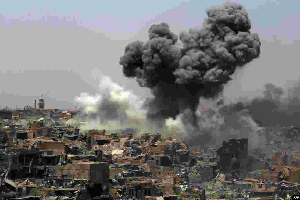 Smoke billows following an airstrike by U.S.-led international coalition forces targeting Islamic State (IS) group in Mosul, Iraq.
