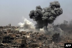 FILE - A picture taken on July 9, 2017, shows smoke billowing following an airstrike by US-led international coalition forces targeting Islamic State (IS) group in Mosul.