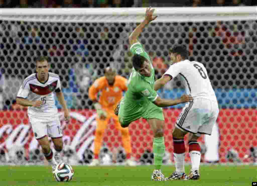 Algeria's Saphir Taider, left, is challenged by Germany's Mesut Ozil (8) during the World Cup round of 16 soccer match between Germany and Algeria at the Estadio Beira-Rio in Porto Alegre, Brazil, Monday, June 30, 2014. (AP Photo/Sergei Grits)