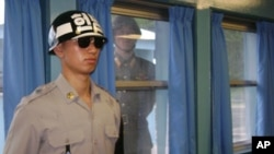 Một binh sĩ Bắc Triều Tiên nhìn qua khung cửa sổ, trong lúc một binh sĩ Nam Triều Tiên đứng gác tại làng Bàn Môn Điếm, 21/7/2010