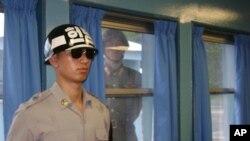 在朝鲜半岛北纬三十八度停战线上的村落板门店非军事区,韩国宪兵在联合国停战村站岗,朝鲜一名士兵在窗后观察。(资料照片)