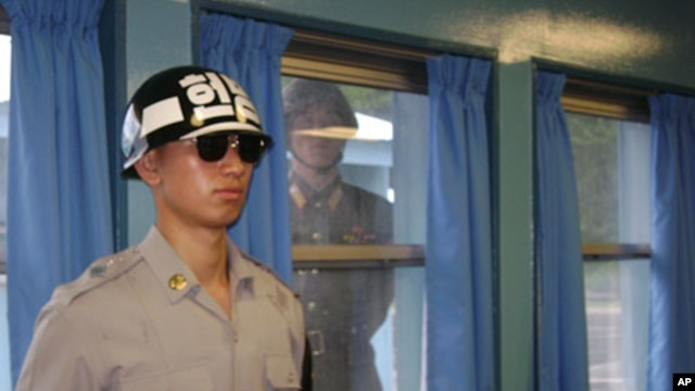 A North Korean soldier looks through a window as a South Korean stands guard at the U.N. truce village building that sits on the border of the Demilitarized Zone in Panmunjon, South Korea. (File)