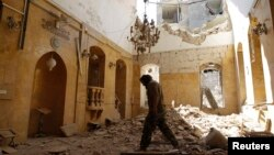 A man walks inside a mosque damaged by, according to activists, a barrel bomb thrown by forces loyal to Syria's president Bashar Al-Assad in Old Aleppo, May 1, 2014.