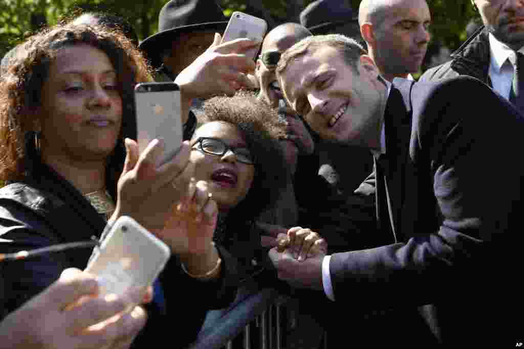 President-elect Emmanuel Macron, poses for a picture with supporters after a ceremony to mark the anniversary of the abolition of slavery in Paris, France.
