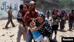 Keluarga Palestina di Jalur Gaza berlarian menyelamatkan diri dari serangan udara Israel, Rabu (9/7).