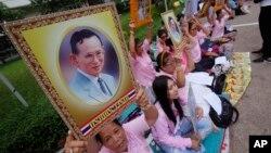 ពលរដ្ឋថៃធ្វើការបួងសួង និងកាន់រូបព្រះឆាយាល័ក្ខរបស់ស្តេច Bhumibol Adulyadej នៅមន្ទីរពេទ្យ Siriraj កាលពីថ្ងៃទី១២ ខែតុលា ឆ្នាំ២០១៦។