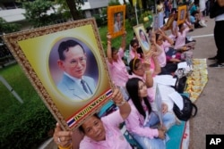 Thais pray while holding up portraits of Thailand's King Bhumibol Adulyadej at Siriraj Hospital where the king is being treated in Bangkok, Thailand, Oct. 12, 2016.