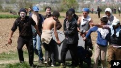Para migran mengangkut seorang pria yang terluka dengan selimut dalam protes di Idomeni, Yunani (10/4). (AP/Amel Emric)
