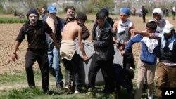Мігранти несуть пораненого товариша в Ідомені