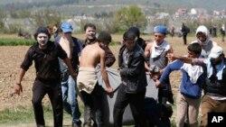 Migranti nose ranjenog čoveka posle sukoba sa policijom u Idomeniju, 10. april, 2016.