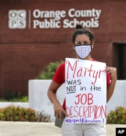 FILE - In this Tuesday, July 7, 2020 file photo, Rachel Bardes holds a sign in front of the Orange County Public Schools headquarters as teachers protest with a car parade in Orlando, Fla. (Joe Burbank/Orlando Sentinel via AP, File)