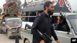 Anggota pasukan keamanan Pakistan memeriksa warga suku Khyber di Peshawar, Pakistan (6/11). (AP/Mohammad Sajjad)