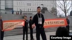 袁冬等人2013年3月31日在北京西单展示反腐横幅呼吁官员公示财产。后来袁冬被判刑一年半(微博图片)