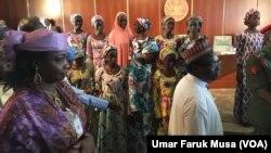 Le président nigérian Muhammadu Buhari et les lycéennes de Chibok libérées récemment.