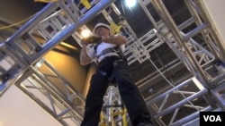 3M's Steve Kosch demonstrates a safety harness and escape system at Offshore Tech Conf Houston. (G. Flakus/VOA)