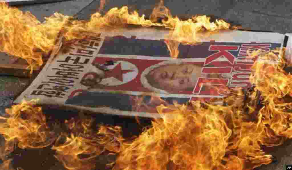A picture of North Korean leader Kim Jong Un is burned by anti-North Korea protesters during an anti-North Korea rally denouncing North Korea's long-range rocket launch in Seoul, South Korea, Friday, April 13, 2012. (AP Photo/Lee Jin-man)