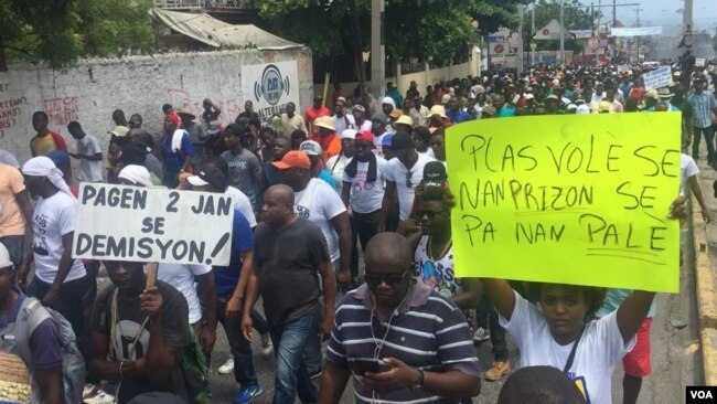 "PetroCaribe anti-corruption protesters make their way around the capital, Port-au-Prince, to demand the president's resignation. One poster reads: ""There are no two ways about it, resign."" The other reads: ""Thieves belong in prison, not in the palace."" (M. Vilme/VOA Creole)"