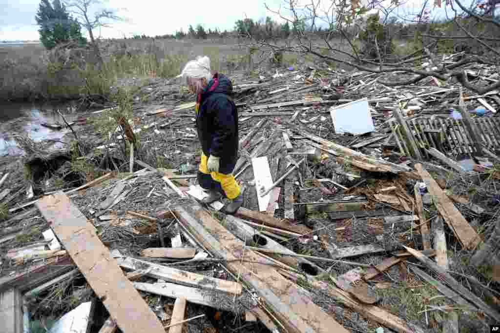 Tricia Burke walks over debris which washed up onto her property in the wake of superstorm Sandy, Nov. 1, 2012, in Brick, N.J.
