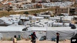 FILE - Syrian refugee children play at an informal refugee camp, which is seen set between the houses and buildings in Arsal, near the border with Syria, east Lebanon, June 13, 2018.